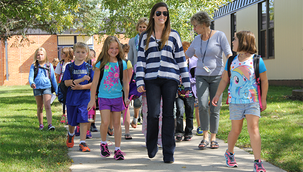 Students and teachers walk down a sidewalk at Sibley Elementary School on Friday to meet waiting parents and school buses. — Tim Engstrom/Albert Lea Tribune