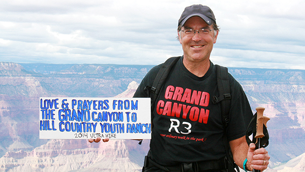Albert Lea volunteer assistant cross country coach Bryce Gaudian stands with his trekking pole and a sign for Hill Country Youth Ranch while hiking the Grand Canyon. — Provided