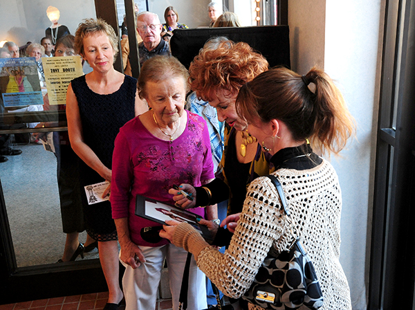 A woman has Marion Ross autograph a photo the two took together when she was a young girl. — Brandi Hagen/Albert Lea Tribune