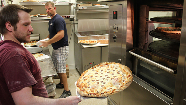 An employee takes a fresh pizza out of the oven at Jake's Pizza during the lunch hour on Sept. 19. – Tim Engstrom/Albert Lea Tribune