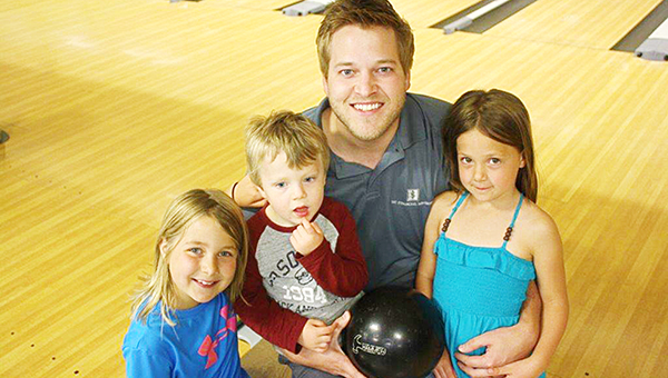 Jon Murray sits with his children after bowling his second career perfect game in the Service Club League. He used an old house ball off the rack, which was the same ball he used when he scored his first 300 game. Holiday Lanes gave the ball to Murray. — Provided