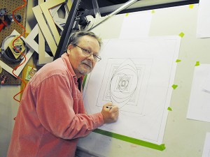 Steve Larson stands in front of his drafting table, working on one of his geometric paintings. – Provided