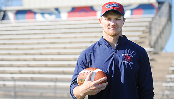 Josh Bain, an assistant football and wrestling coach at Albert Lea High School, holds a football on Jim Gustafson Field. He teaches physical education and a few other subjects, too. – Micah Bader/Albert Lea Tribune