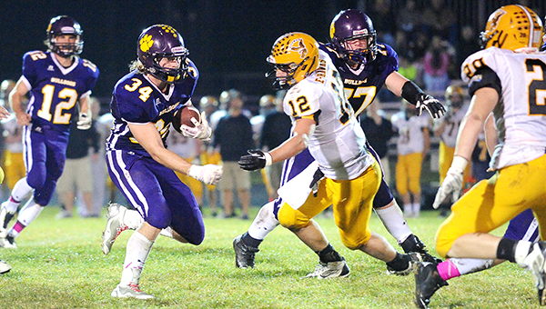 Andrew Olsen of Lake Mills carries the ball up the middle Friday as Zach Throne blocks Zach Anderson of Emmetsburg. — Micah Bader/Albert Lea Tribune