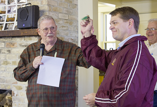 Tony Trow, left, returns the keys to the Edgewater Cottage to Albert Lea Mayor Vern Rasmussen on Saturday during a celebration at the cottage. A group of volunteers recently completed renovating the building. – Sarah Stultz/Albert Lea Tribune