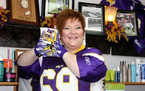 Käri Fjeldberg stands in her salon inside Dinah's Style wearing a Jared Allen jersey and Minnesota Vikings gloves.