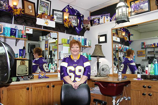 Käri Fjeldberg wears a Jared Allen jersey in her salon inside Dinah's Style next to some Minnesota Vikings memorabilia.