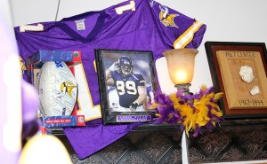 A framed photo of former Minnesota Vikings defensive tackle Chris Hovan sits on a shelf next to a few authenticated pieces of Metropolitan Stadium — where the Vikings played until 1981 — at Käri Fjeldberg's salon inside Dinah's Style.