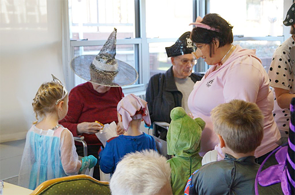 Children collect candy from residents at St. John's Lutheran Community for Halloween on Friday. — Provided