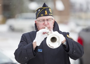 """""""Taps"""" is played during a snowy and cold Veterans Day program Tuesday outside of Freeborn County Courthouse. – Colleen Harrison/Albert Lea Tribune"""
