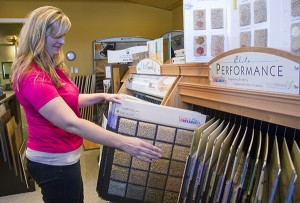 Tiffany Kriesel of Freeborn Lumber Co. & Design shows the several varieties of carpet available at the business. – Sarah Stultz/Albert Lea Tribune