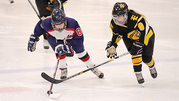 Maddy Carstens of Albert Lea skates with the puck, while Mankato East/Loyola's Taylor Kanstrup defends Tuesday at Albert Lea City Arena. Carstens scored a pair of goals in the Tigers' loss. — Micah Bader/Albert Lea Tribune