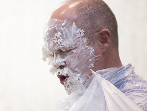 Tim Madson, a physical medicine and rehabilitation manager at Mayo Clinic Health System in Albert Lea, tries to manuever some whipped cream off of his face after getting hit with a pie Thursday. — Colleen Harrison/Albert Lea Tribune