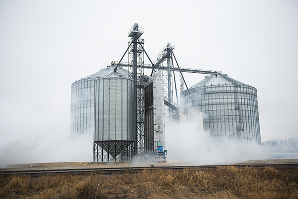 Anhydrous ammonia billows past grain bins at the WFS grain elevator Monday in Clarks Grove after a leak was discovered in a the tank of a semi. Part of Clarks Grove was evacuated as the gas can be harmful and potentially lethal if breathed in. – Colleen Harrison/Albert Lea Tribune