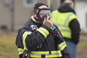 A firefighter from Geneva Fire Department secures an oxygen mask while preparing to respond to an anhydrous ammonia gas leak Monday at Clarks Grove Fertilizer. – Colleen Harrison/Albert Lea Tribune