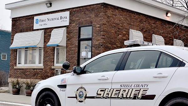 A Steele County sheriff's patrol car sits outside the First National Bank in Hope Friday morning. Steele County Sheriff Lon Thiele said that a man held up the bank at gunpoint Friday morning. -- Matt Hudson/Owatonna People's Press