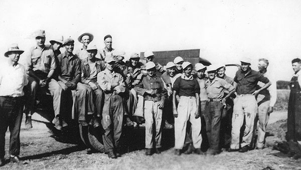 Henry Stensrud in July 1945 at a pea viner station near Hartland with German prisoners of war. Stensrud is third from left on the truck bed, while the rest of the men around him are POWs. All were housed at the POW camp in Wells. — Photo courtesy Wells Depot Museum
