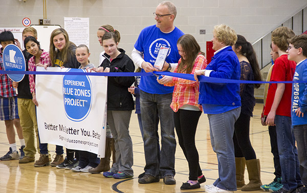 Sixth-grader Lydia Levi, center, cuts a ribbon during a ceremony celebrating Southwest Middle School as the first Blue Zones designated school in Albert Lea on Friday. - Sarah Stultz/Albert Lea Tribune