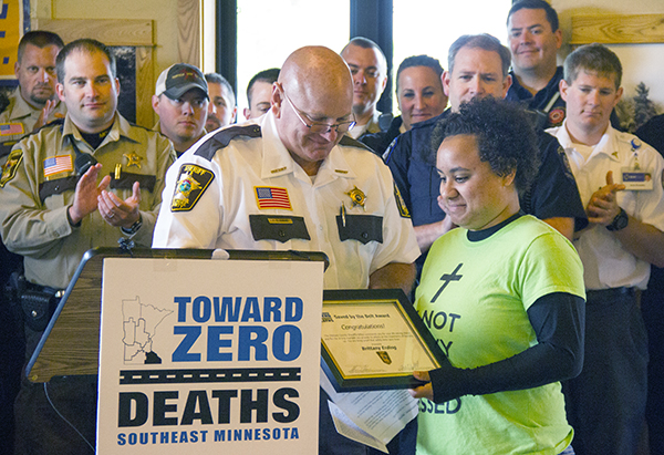Fillmore County Sheriff Tom Kaase presents Brittany Erding of Preston a Saved by the Belt Award on Monday during a news conference at the Edgewater Park pavilion. - Sarah Stultz/Albert Lea Tribune