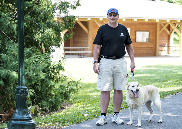 Larry Larson of Albert Lea stands with Magnum, his labrador retriever, on a hiking trail on the north side of Fountain Lake.