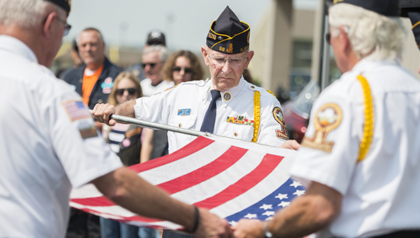 Members of Albert Lea American Legion Post 56 roll up a flag presented to the Albert Lea chapter of the Harley Owner's Group Tuesday at Bergdale Harley-Davidson as a part of the Nation of Patriots Tour. The flag is being escorted through all 48 of the continental United States. - Colleen Harrison/Albert Lea Tribune