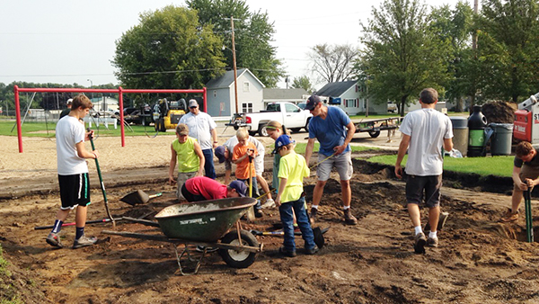 Students Logan Studier, Isaac Hornberger, Reece Nelson, Justine Nelson, Logan Hajek, Ethan Hajek and faculty members Lucas Knutson and Jared Eastvold assist a Titan Machinery employee and playground installation contractor on Monday. - Provided