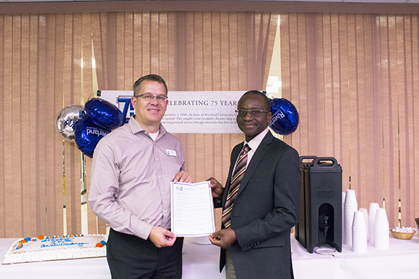 Albert Lea City Manager Chad Adams presents Riverland Community College President Adenuga Atewologun with the Mayor's Riverland Community College Proclamation recognizing the college's 75th anniversary during an open house at the school on Tuesday. - Kelly Wassenberg/Albert Lea Tribune