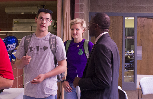 Riverland Community College President Adenuga Atewologun speaks with Riverland students Jared Larson and Jenni Golbuff at the college's 75th anniversary open house  on Tuesday in the Skylight room. Atewologun was also present at the open house in Owatonna earlier in the day. - Kelly Wassenberg/Albert Lea Tribune