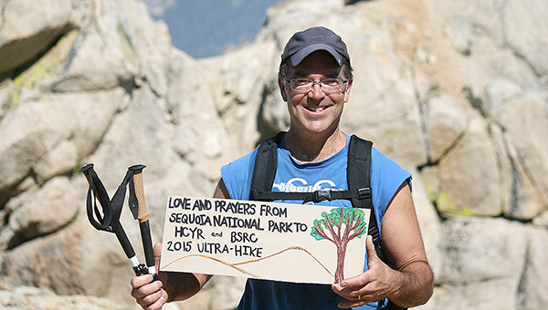 Bryce Gaudian of the Hayward area stands on the Alta Peak in Sequoia National Park at an elevation of 11,207 feet. He holds a sign for the children at Hill Country Youth Ranch and Big Springs Ranch for Children. — Provided