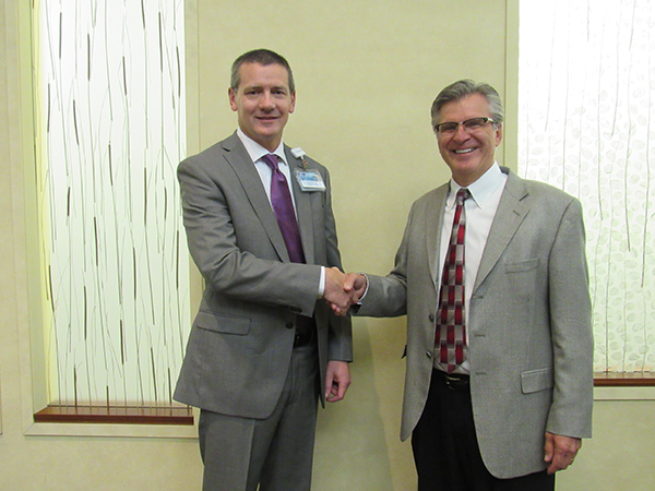 Mark Ciota, orthopedic surgeon and chief executive officer at Mayo Clinic Health System in Albert Lea and Austin, presents Scot Sates, CEO and administrator of St. John's Lutheran Community, with a donation to go toward a new wellness area. -Provided