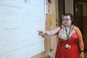 Instructor Kelly Weitzel discusses math problems about finding the square root and cube root of different numbers. - Sarah Stultz/Albert Lea Tribune