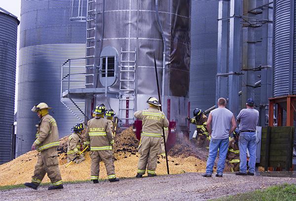 Firefighters remove grain from the grain dryer Wednesday morning south of Glenville—Sam Wilmes/Albert Lea Tribune