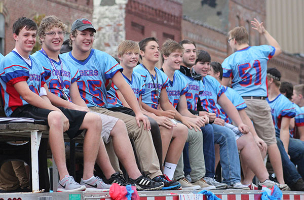 Albert Lea High School football players pose for photos while in the Homecoming parade Wednesday evening in downtown Albert Lea. -Sarah Stultz/Albert Lea Tribune