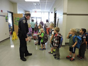 School resource officer Ryan Murphy can often be seen accepting high fives from elementary students at USC. - Kelly Wassenberg/Albert Lea Tribune