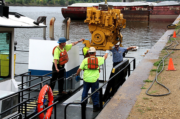 Workers at Upper River Services lower a new engine into the towboat Becky Sue. — Tim Nelson/MPR News