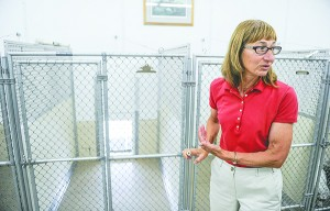 Andrea McConico shows off the easy to open kennel gates that allow the dogs to exit outside to outdoor kennels. - Eric Johnson/Albert Lea Tribune