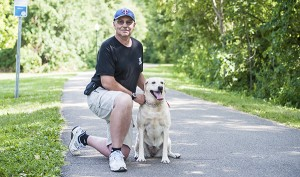Larry Larson of Albert Lea kneels with Magnum, his labrador retriever, on a hiking trail on the north side of Fountain Lake. - Micah Bader/Albert Lea Tribune