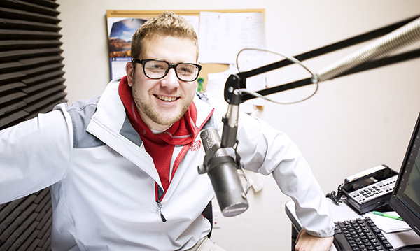 Mitchell Widmeier sits in a studio Tuesday at KATE radio. Widmeier was hired as the station's sports director and has announced three Albert Lea football games. - Micah Bader/Albert Lea Tribune