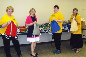 Diane Doppelhammer, Denise Sandager, Joan Anderson and Jane Pearson stand with some of the school bags made during the effort. - Provided