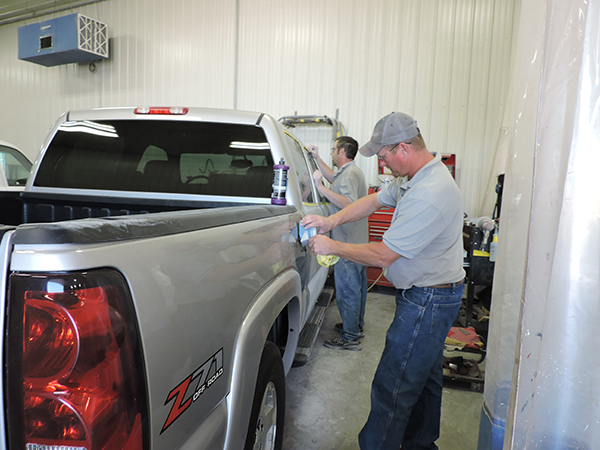 Tim Cliff uses the AkzoNobel Automatchic Vision to determine the paint color of Chevy Silverado being worked on in his shop while one of his employees continues to do prep work on the vehicle. - Kelly Wassenberg/Albert Lea Tribune