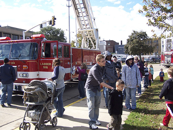 Children wait in line with their parents to try out the fire hose at the Albert Lea Fire Department Open House in 2011. -Provided