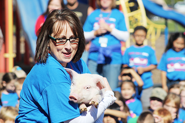 Sibley Elementary School Principal Diane Schultz prepares to kiss a pig Friday outside the school after the students completed their Stroll for a Goal. They raised more than $23,000. - Sarah Stultz/Albert Lea Tribune
