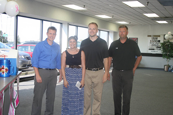 Representatives of Dave Syverson Auto Center present a check for $4,500 to Justin and Erin Mikels. A portion of the profits for the cars that were sold between July 15 and August 15 went to the Mikels family to help with the expense of Erin Mikels' cancer treatments. - Provided