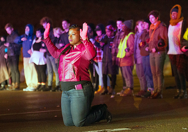 A protester kneels in front of others on Interstate 94 in Minneapolis Monday, refusing to leave after police declared the gathering illegal. Many were arrested. - Judy Griesedieck/For MPR News