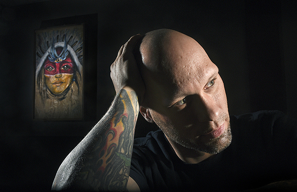 """""""The money is just a number. What I really want is my life back,"""" said 38-year-old Michael Hansen at his tattoo shop, Kinship Collective Tattoo, in Northfield. Hansen is one of the first people under a new Minnesota exoneration law to qualify for financial compensation for time spent locked up. - Richard Marshall/ for MPR News"""