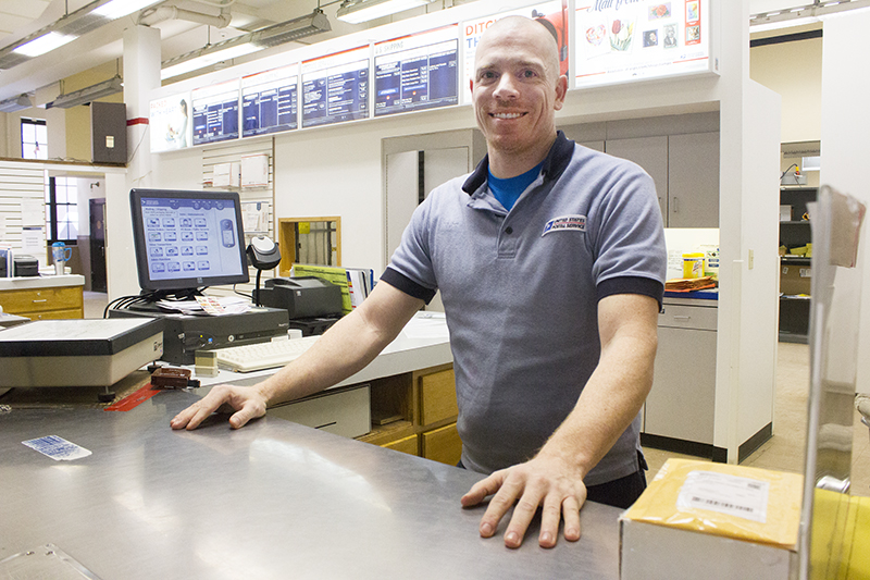 U.S. Postal Service clerk Tony Stangeland looks to bring a smile to customers' faces — one at a time. - Sam Wilmes/Albert Lea Tribune