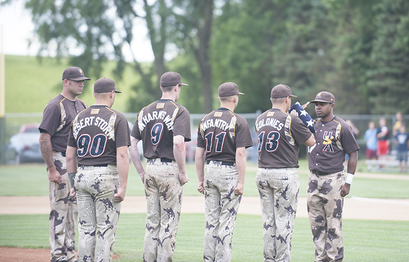 The U.S. Military All-Stars honor the flag of The United States of America before the game Thursday evening at Hayek Field.