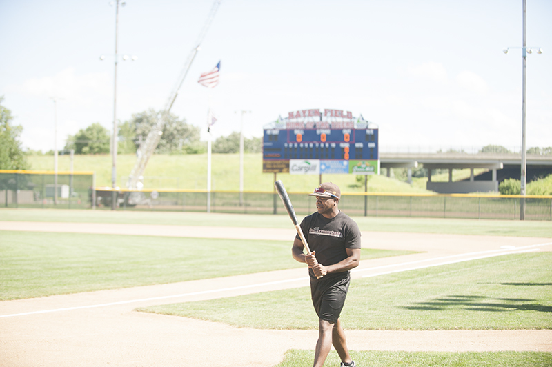 Lesean Thomas (Air Force) takes a look at his bat as he heads toward the batting cage for some batting practice before Thursday's game against the Albert Lea Lakers.