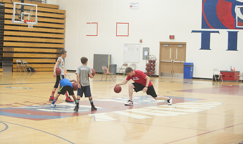 Novosad, right, teaches some young, future basketball players dribbling drills during one of his skill sessions earlier in July.