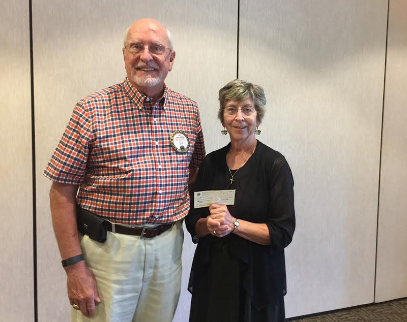 Lion Jim Broberg presents Lilah Aas with a donation for $100 for the Habitat 500, a 500 mile bike ride that raises funds for Habitat for Humanity.  This was Aas' 20th year of riding.  -Provided